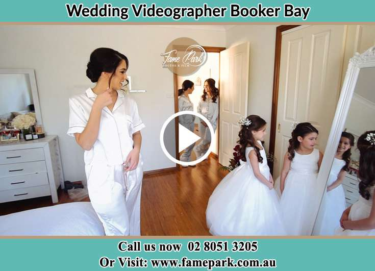 Bride looking at the mirror with her secondary sponsors Booker Bay NSW 2257