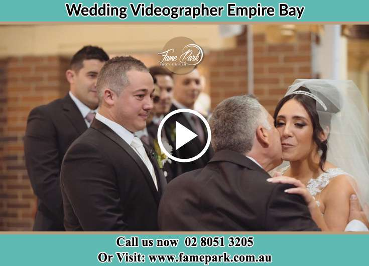Bride and his father kissed her at tne ceremony Empire Bay NSW 2257