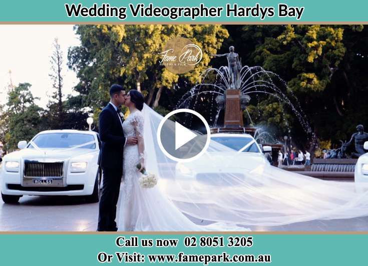 Bride and Groom kissed nesr the bridal car Hardys Bay NSW 2257