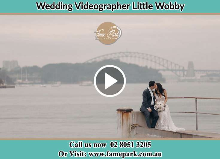 Bride and Groom kissed while sitting on near the shore Little Wobby NSW 2256