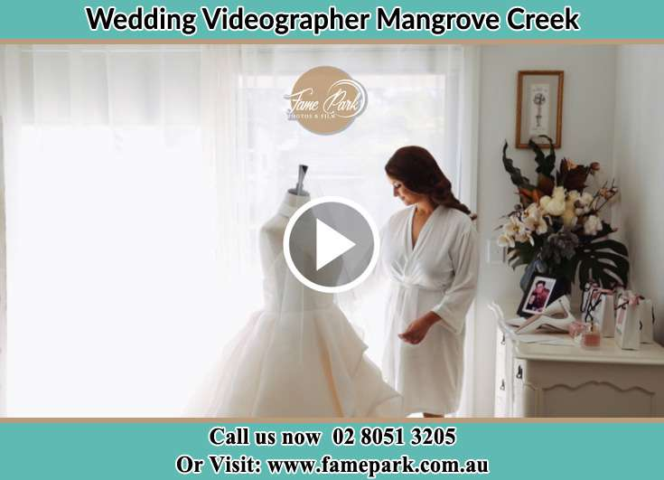 Bride looking at her wedding gown Mangrove Creek NSW 2250