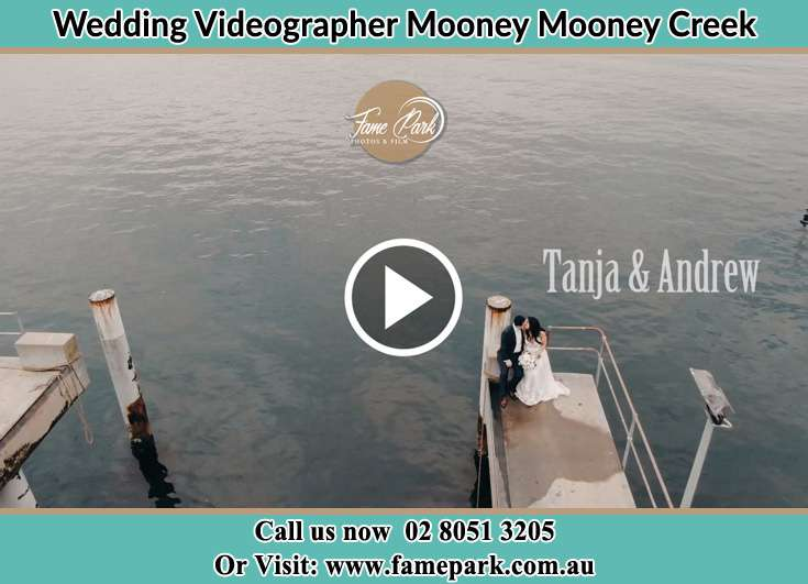 Bride and Groom kissed while sitting at the bay walk Mooney Mooney Creek NSW 2250