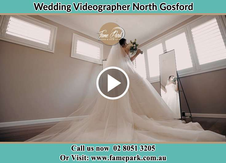 Bride in front of the mirror while holding a bouquet of flowers North Gosford NSW 2250