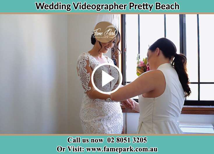A Bridesmaid helps the Bride getting ready for the wedding Pretty Beach NSW 2257